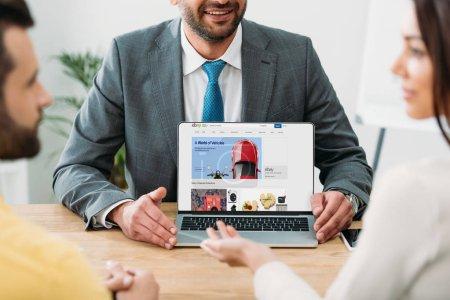 Photo pour Recadrée vue du conseiller assis à table et portable avec ebay site Web sur l'écran avec les investisseurs au bureau - image libre de droit