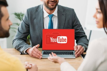 Photo pour Recadrée vue du conseiller assis à table et portable avec youtube site Web sur l'écran avec les investisseurs au bureau - image libre de droit