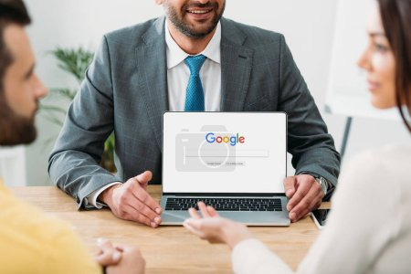 Photo pour Recadrée vue du conseiller assis à table et portable avec google site Web sur l'écran avec les investisseurs au bureau - image libre de droit