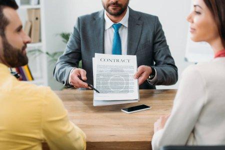 Photo pour Recadrée vue du conseiller assis à table et poinping avec un stylo à contrat aux investisseurs au bureau - image libre de droit