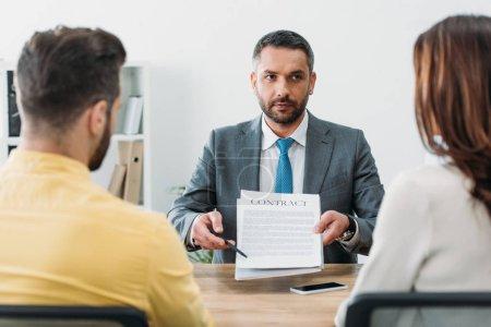 Photo pour Mise au point sélective du conseiller assis à table et poinping avec un stylo à contrat aux investisseurs au bureau - image libre de droit
