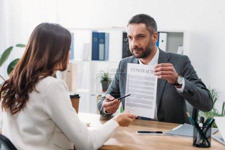 Photo pour Orientation sélective du conseiller assis à la table et pointant du doigt le contrat avec la plume vers la femme en fonction - image libre de droit