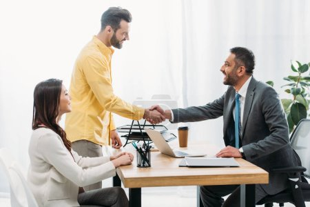 Photo for Advisor and investor shaking hands over table wile woman sitting in office - Royalty Free Image