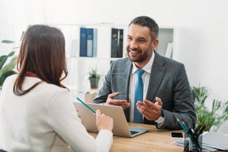 Photo pour Mise au point sélective du conseiller assis à table avec ordinateur portable et de la femme dans le bureau - image libre de droit