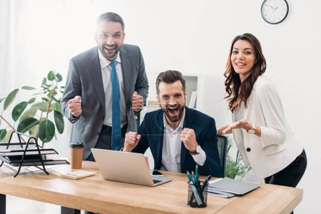 Photo for Colleagues at table looking to laptop, rejoicing and smiling in office - Royalty Free Image