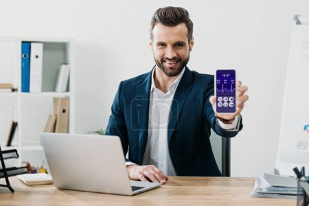 Photo pour Homme d'affaires assis à table avec ordinateur portable et montrant le smartphone avec commerce graphique app sur écran au bureau - image libre de droit
