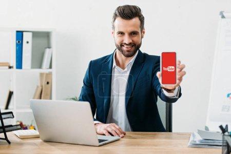 Photo pour Homme d'affaires assis à table avec ordinateur portable et montrant le smartphone avec l'application youtube sur écran au bureau - image libre de droit