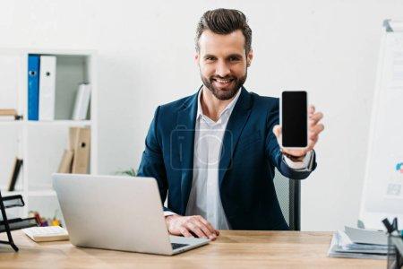 Photo pour Homme d'affaires assis à table avec ordinateur portable et montrant le smartphone avec écran blanc au bureau - image libre de droit