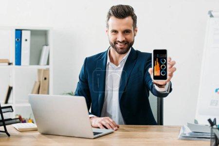 Photo pour Homme d'affaires assis à table avec ordinateur portable et montrant le smartphone avec application des graphiques sur écran au bureau - image libre de droit