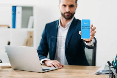 Photo pour Mise au point sélective d'homme d'affaires assis à table avec ordinateur portable et montrant le smartphone avec Skype app sur écran au bureau - image libre de droit