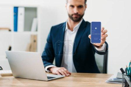 Photo pour Mise au point sélective d'homme d'affaires assis à table avec ordinateur portable et montrant le smartphone avec l'application facebook sur écran au bureau - image libre de droit