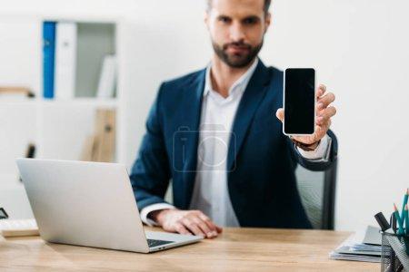 Photo pour Mise au point sélective d'homme d'affaires assis à table avec ordinateur portable et montrant le smartphone écran blanc au bureau - image libre de droit