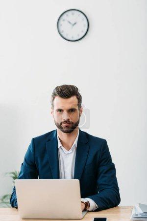 Photo pour Homme d'affaires en costume bleu assis à table avec ordinateur portable au bureau - image libre de droit