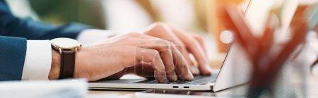 Photo pour Vue recadrée de l'homme d'affaires assis à table avec ordinateur portable et dactylographier dans le bureau - image libre de droit