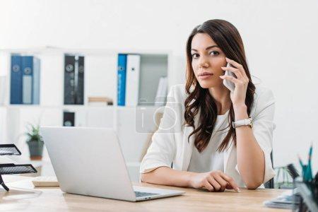 Photo pour Femme d'affaires assis à table avec ordinateur portable et de parler sur smartphone au bureau - image libre de droit