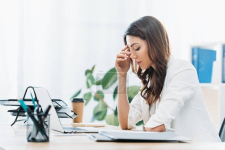 Photo for Upset businesswoman sitting at table and looking to laptop in office - Royalty Free Image