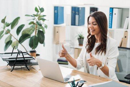 Photo pour Femme d'affaires assis à table avec ordinateur portable et le pouce se lève au bureau - image libre de droit