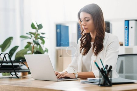 Photo for Attractive businesswoman sitting at table with laptop and typing in office - Royalty Free Image