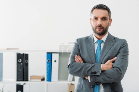 Photo for Handsome businessman standing with crossed arms in office - Royalty Free Image