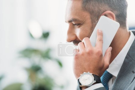 Photo for Handsome businessman talking on smartphone in office - Royalty Free Image