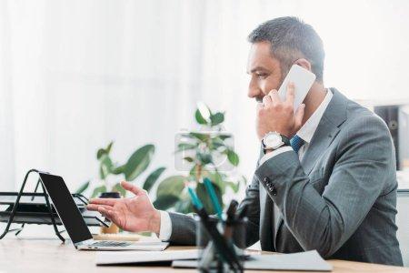 Photo pour Bel homme d'affaires assis à table avec ordinateur portable et de parler sur smartphone au bureau - image libre de droit