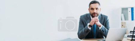 Photo pour Homme d'affaires assis à table avec ordinateur portable et regardant la caméra dans le bureau - image libre de droit