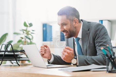 Photo pour Bel homme d'affaires assis à table, à la recherche d'ordinateur portable et montrant le geste oui au bureau - image libre de droit