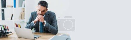 Photo pour Bel homme d'affaires en costume gris, assis à table avec ordinateur portable et de penser au bureau - image libre de droit