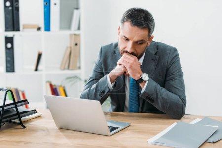 Photo pour Bel homme d'affaires assis à table avec ordinateur portable et de penser au bureau - image libre de droit