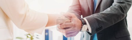 Photo for Cropped view of man and woman shaking hands at office - Royalty Free Image