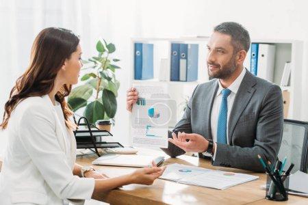 Photo pour Beau conseiller examen du document avec les investisseurs au bureau - image libre de droit
