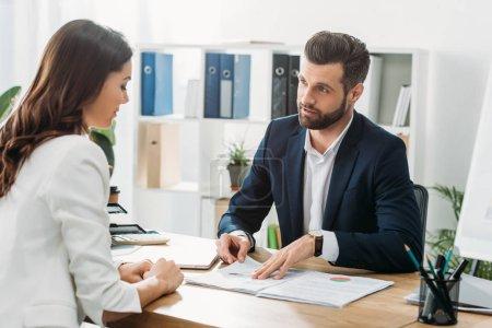 Photo pour Beau conseiller examen du document avec l'investisseur à l'espace de travail - image libre de droit