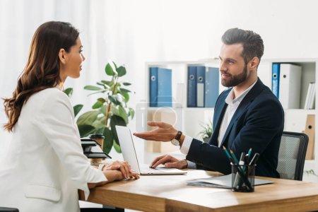 Photo pour Beau conseiller en costume parler avec belle investisseur au bureau - image libre de droit