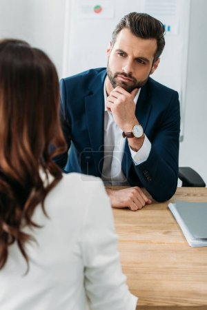 Photo for Selective focus of focused and handsome advisor talking with investor at office - Royalty Free Image