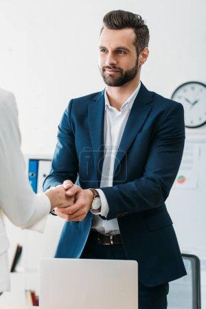 Photo pour Conseiller de beau en costume, serrant la main de l'investisseur à l'espace de travail - image libre de droit