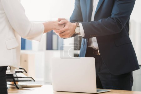 Photo for Cropped view of man shaking hands with woman at office - Royalty Free Image