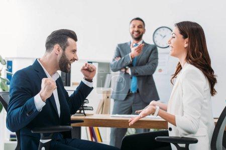 Photo pour Mise au point sélective des investisseurs en costume avec beau conseiller souriant sur fond au bureau - image libre de droit