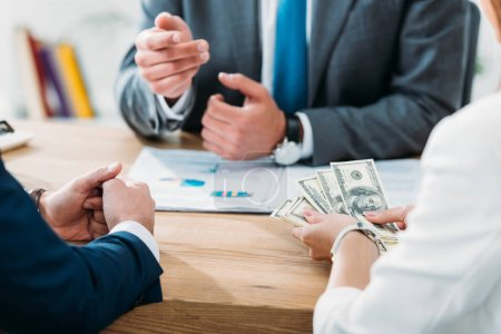 Photo for Selective focus of investor holding money with colleagues at office - Royalty Free Image