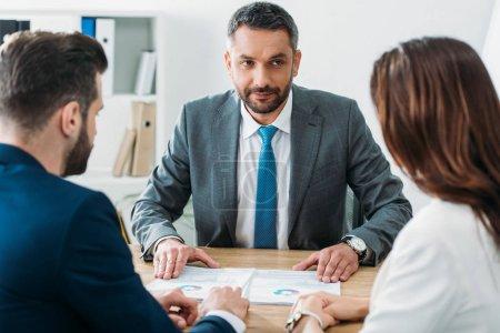 Photo pour Mise au point sélective du conseiller beau parler de document avec des investisseurs à l'espace de travail - image libre de droit
