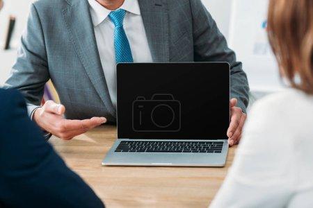 Photo pour Mise au point sélective de conseiller en pointant avec doigts à ordinateur portable avec écran blanc - image libre de droit