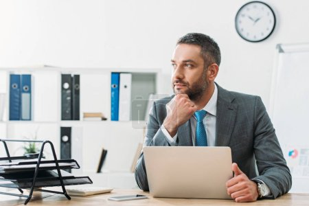 Photo for Handsome advisor in suit looking away with laptop on table - Royalty Free Image