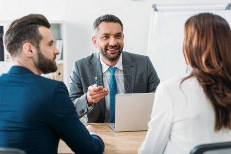 Photo pour Mise au point sélective du beau conseiller en costume de parler avec les investisseurs au bureau - image libre de droit