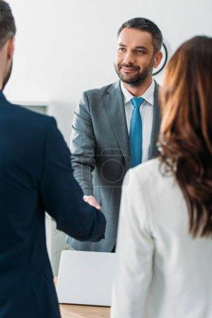Photo pour Mise au point sélective du beau conseiller en costume agitation des mains avec les investisseurs au bureau - image libre de droit