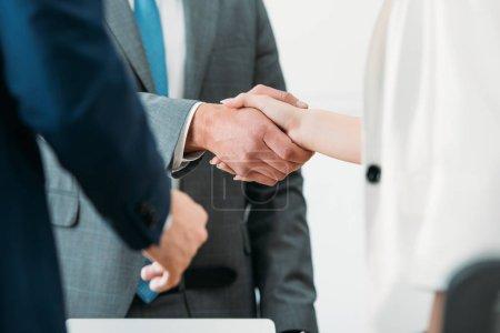 Photo pour Mise au point sélective d'homme et femme se serrant la main au bureau - image libre de droit