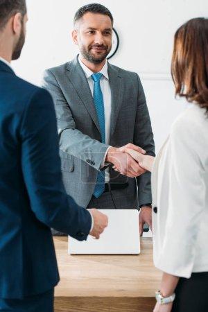 Photo pour Mise au point sélective du conseiller beau costume et investisseurs se serrant la main au milieu de travail - image libre de droit