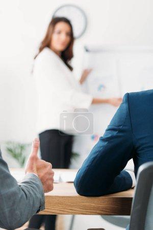 Photo pour Mise au point sélective d'investisseur avec ups de pouce et de femme sur fond - image libre de droit