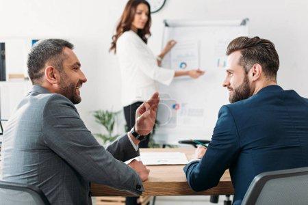 Photo pour Mise au point sélective des investisseurs beau en costume, parler et sourire au milieu de travail - image libre de droit