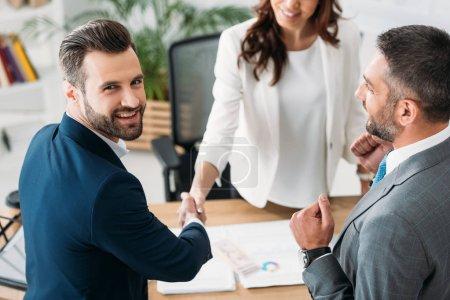 Photo pour Mise au point sélective du conseiller en costume et investisseur beau serrer la main au milieu de travail - image libre de droit