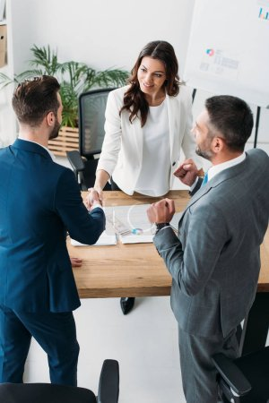 Photo pour Belle conseiller et investisseur beau serrer la main au milieu de travail - image libre de droit
