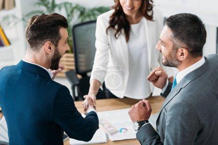 Photo pour Mise au point sélective de conseiller et investisseur beau serrer la main au milieu de travail - image libre de droit